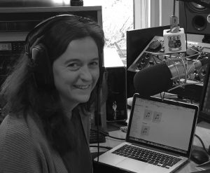 A black and white shot of Abigail Joffe in studio at the radio station